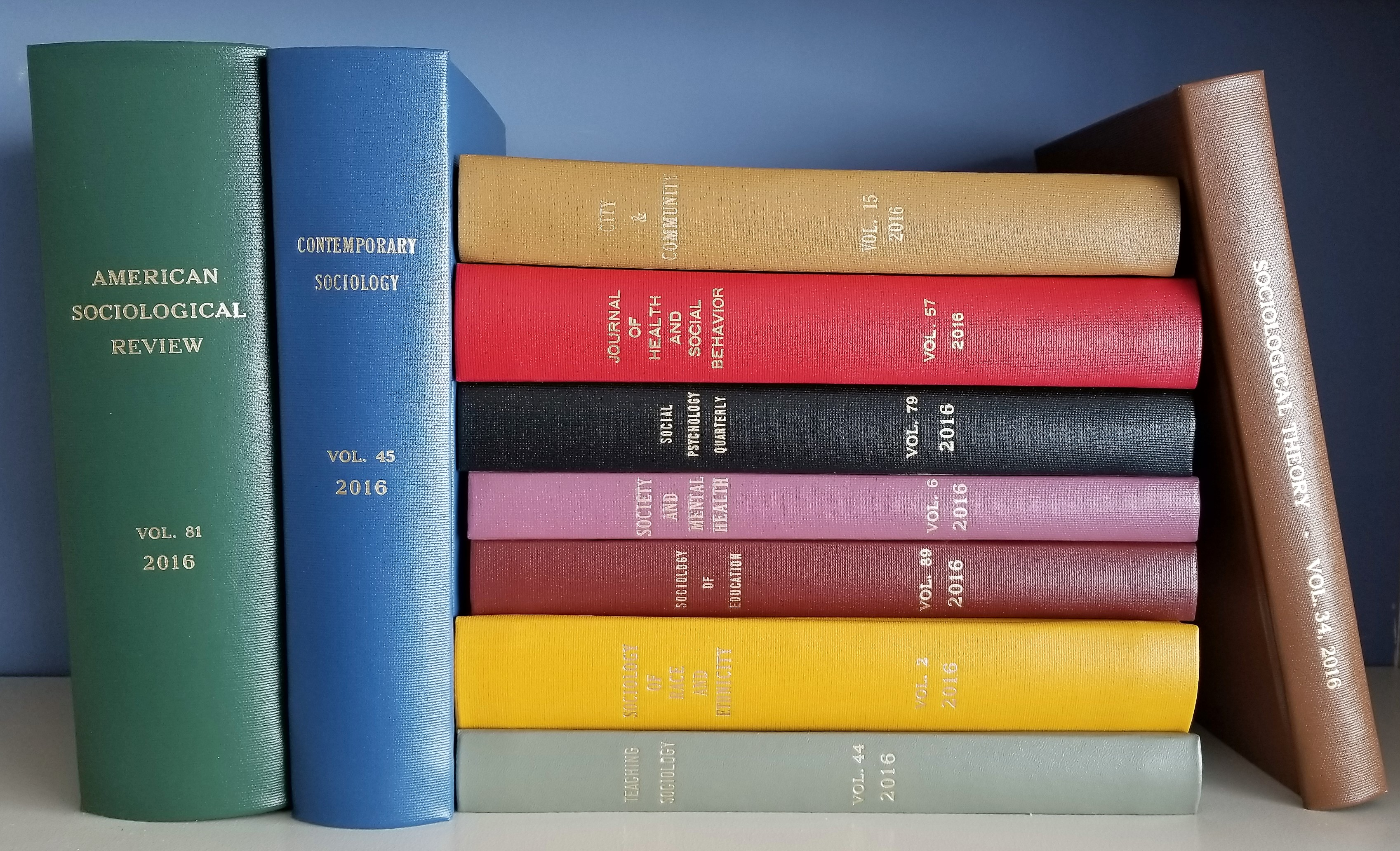 Spines of ASA bound journals stacked and leaning against each other on a white shlef witha blue background.