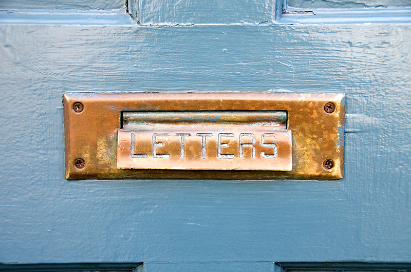 Gold letter slot on a blue door.