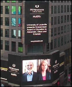 Grawemeyer award winners, Karl Alexander and Doris Entwisle, appear above Times Square