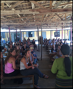 Semester at Sea students learning and listening at a Burmese school.