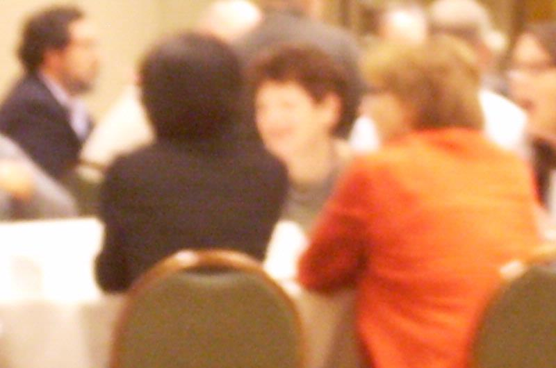 Conference attendees sit around a table