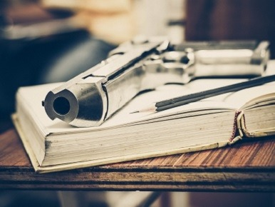 Image of gun on top of book and pencil