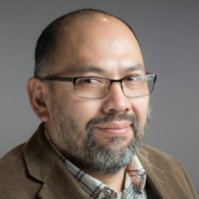 Latino man with bald head, glasses and goatee looking at camera with a side angle and a slight smile..