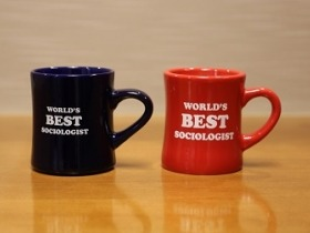 Red and blue diner mugs that have World's Best Sociologist written in white on the side.