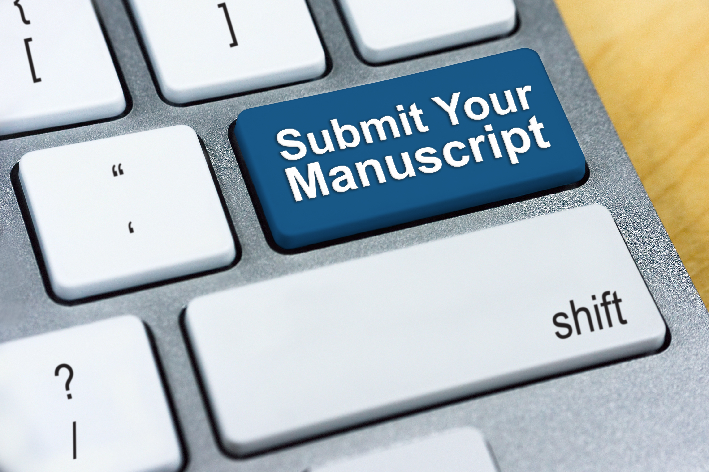 "Keyboard with a blue button that says ""Submit Your Manuscript"" in white letters."
